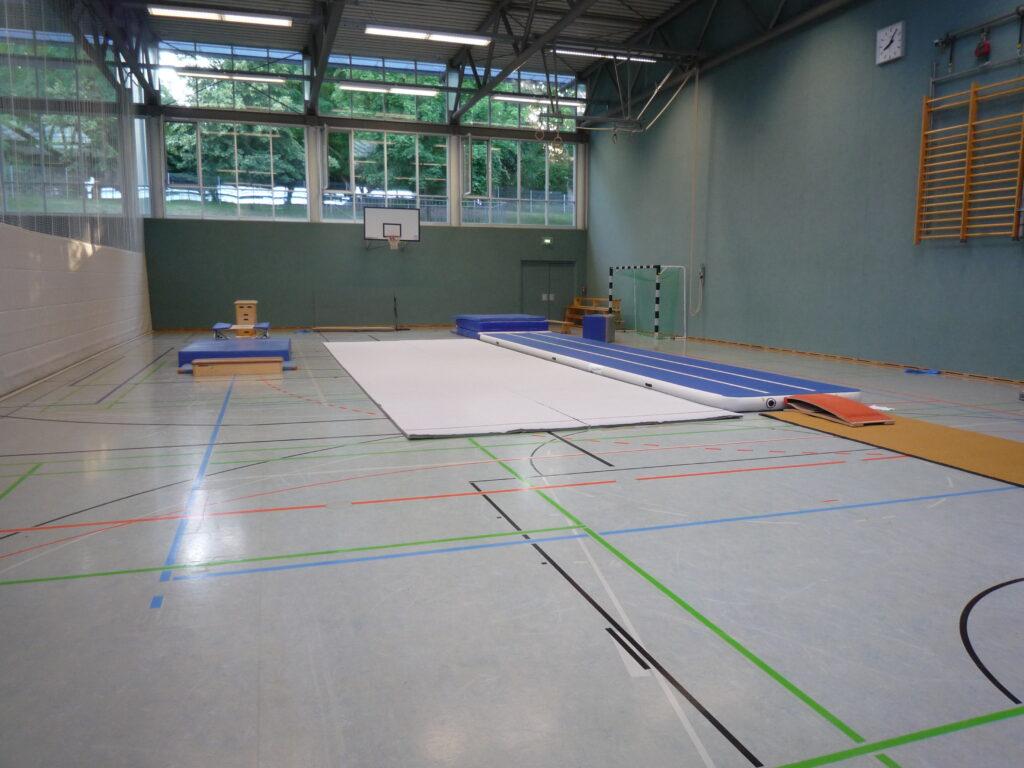 Sporthalle mit einem langen Matten um darauf zu laufen, einem Trampolin und einer Bahn die einem beim aufkommen nach oben federt
